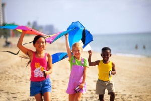 Mixed ethnic children playing on beach flying kites having fun togethe